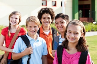 Children standing outside school with bookbags